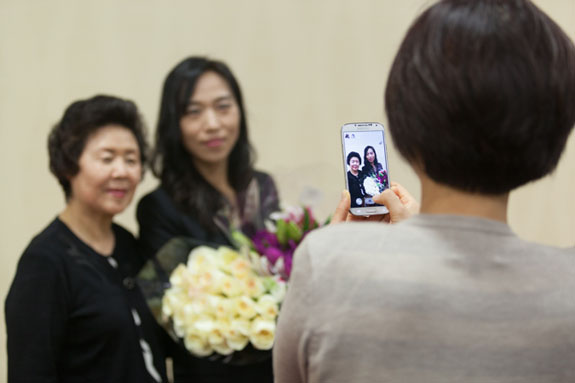 A family member gets an intimate portrait of attorney Youn Lee with her family.   <em>Photo by S. Todd Rogers</em>